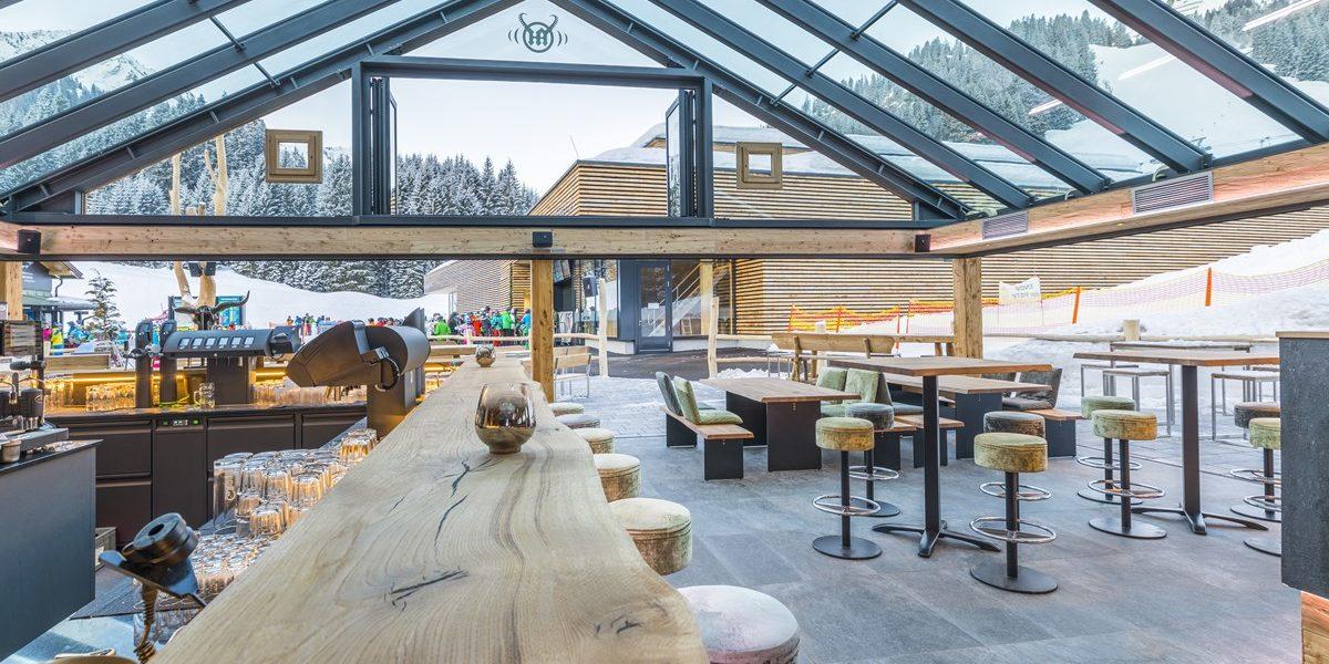 Lichtdurchflutete Bar, Holztheke, Holztische